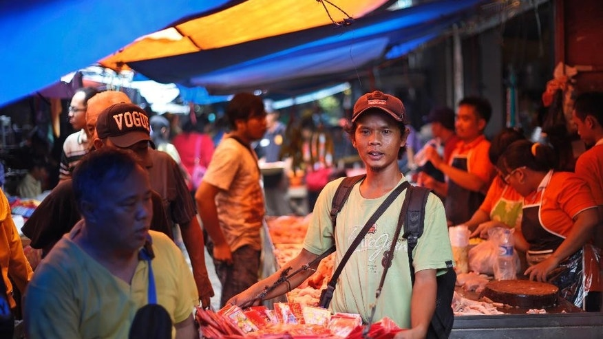 "In this photo taken on Tuesday, Feb. 17, 2015, Maman Rohman, 32, center, sells red envelopes locally known as ""ang pao"" which are used to give money as gifts during Chinese New Year celebrations, at a market in Tangerang, in the outskirts of Jakarta, Indonesia. Rohman, like many other Indonesians, temporarily leave their hometowns and jobs to come to the capital to earn extra money as the Lunar New Year is celebrated by Indonesia's ethnic-Chinese minority.  A farmer from Kuningan, West Java, Rohman said, ""I have come here every year since 1992 … to sell ""ang pao,"" which could get me up to 200,000 rupiah ($17) a day. Not bad at all for a few days of work."" Rohman said business this year is a bit quiet. ""Maybe the Year of the Sheep is just not my year. I got more money last time, so I just hope that next year would be better for me.""  (AP Photo/Dita Alangkara)"