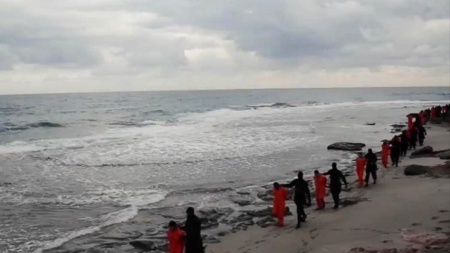 FILE - In this file image made from a video released Sunday, Feb. 15, 2015 by militants in Libya claiming loyalty to the Islamic State group purportedly shows Egyptian Coptic Christians in orange jumpsuits being led along a beach, each accompanied by a masked militant. Libya, virtually a failed state the past years, has provided a perfect opportunity for the Islamic State group to expand from its heartland of Syria and Iraq to establish a strategic stronghold close to European shores. (AP Photo, File)