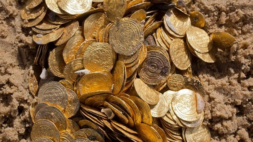 This photo shows a detail of Fatimid period gold coins that were found in the seabed in the Mediterranean Sea near the port of Caesarea National Park in Caesarea, Israel, Wednesday, Feb. 18, 2015. A group of amateur Israeli divers have stumbled upon the largest collection of medieval gold coins ever found in the country, dating back to the 11th century and likely from a shipwreck in the Mediterranean Sea. (AP Photo/Ariel Schalit)