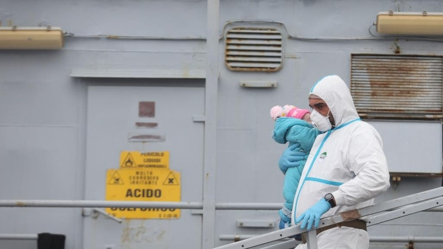 An officer carries a baby as migrants disembark from a tug boat after being rescued in Porto Empedocle, Sicily, southern Italy, Tuesday, Feb. 17, 2015. With Libya's security rapidly deteriorating, the number of migrants who set out in smugglers boats from Libyan shores toward Italy has surged. (AP Photo/Francesco Malavolta)