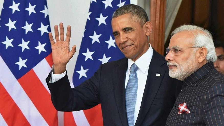In this Jan.25, 2015 file photo, Indian Prime Minister Narendra Modi, right, wears a dark pinstriped suit with his name monogrammed in dull gold stripes as he poses for the media with U.S. President Barack Obama in New Delhi, India. The suit which became controversial after its photographs went viral on social media was to be auctioned in his home state of Gujarat, over the next three days starting Wednesday, Feb.18, 2015 officials said. (AP Photo/Press Trust of India) INDIA OUT