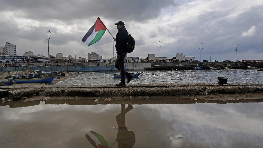 A man holds the Palestinian national flag during a protest calling for reconstruction of houses which were destroyed during last summer's Israel-Hamas war, at fisherman's port in Gaza City, Wednesday, Feb. 18, 2015. (AP Photo/Adel Hana)