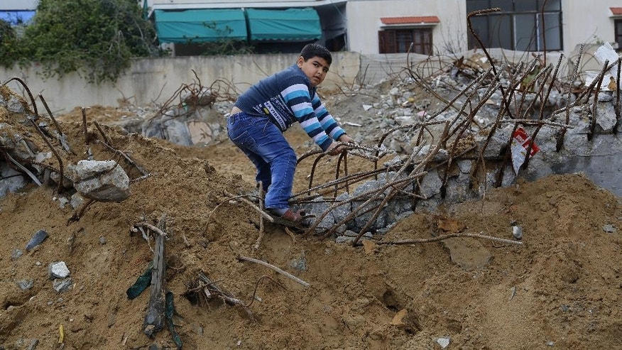 Yousef Nasr, 6, stands in the rubble of Zafer 4 Tower, which was destroyed in the last summer's Israel-Hamas war, during cornerstone ceremony for rebuilding Zafer 4 Tower in Gaza, in the northern Gaza Strip, Wednesday, Feb. 18, 2015. Palestinian officials have laid the cornerstone for the rebuilding of a residential high-rise flattened in last summer's war between the Islamic militant group Hamas and Israel. Wednesday's ceremony by Gaza's public works minister was a symbolic move to boost the spirits of the nearly 500 residents of Zafer 4 Tower, which was hit by two bombs from the air during fighting in August. (AP Photo/Adel Hana)