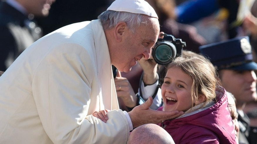 Feb. 18, 2015: Pope Francis caresses a young girl as he arrives for his weekly general audience, in St. Peter's Square, at the Vatican. (AP)