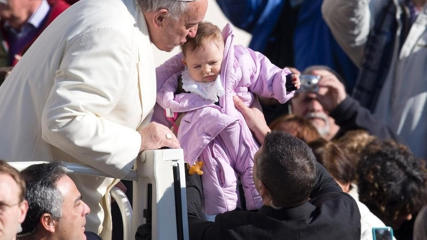 Feb. 18, 2015: Pope Francis kisses a baby as he arrives for his weekly general audience, in St. Peter's Square, at the Vatican. (AP)