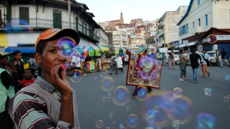 FILE - In this file photo taken Monday, Nov. 22, 2010 a street hawker blows bubbles to attract customers in Antananarivo, Madagascar. President Hery Rajaonarimampianina is on the defensive after a year in office with problems of complaints over bad road that are grid locked and cuts in electricity supplies. (AP Photo/Themba Hadebe, File)