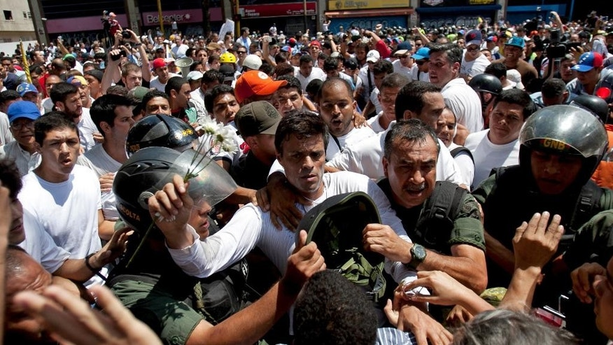 FILE - In this Feb. 18, 2014 file photo, opposition leader Leopoldo Lopez, dressed in white and holding up a flower stem, is taken into custody by Bolivarian National Guards in Caracas, Venezuela. One year has passed since Venezuela's streets were rocked by anti-government protests that left 43 people dead and neighborhoods disrupted by flaming barricades. Wednesday, Feb. 18, 2015 also marked the one year anniversary of Lopez's arrest. (AP Photo/Alejandro Cegarra, File)