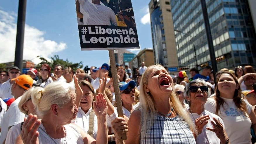 "Supporters of jailed opposition leader Leopoldo Lopez chant slogans demanding his freedom and at an event marking the one year anniversary of his arrest and imprisonment in Caracas, Venezuela, Wednesday, Feb. 18, 2015. One year has passed since Venezuela's streets were rocked by anti-government protests that left 43 people dead and neighborhoods disrupted by flaming barricades. The unrest culminated with the arrest of Lopez, a former Caracas-area mayor and key opposition leader. The sign reads in Spanish ""Free Leopoldo."" (AP Photo/Ariana Cubillos)"