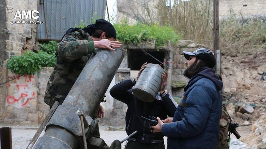 This photo provided on Sunday Feb. 15, 2015 by the Syrian anti-government activist group Aleppo Media Center (AMC), which has been authenticated based on its contents and other AP reporting, shows Syrian rebels preparing to fire locally made shells against the Syrian government forces, in Aleppo, Syria. (AP/Aleppo Media Center, AMC)