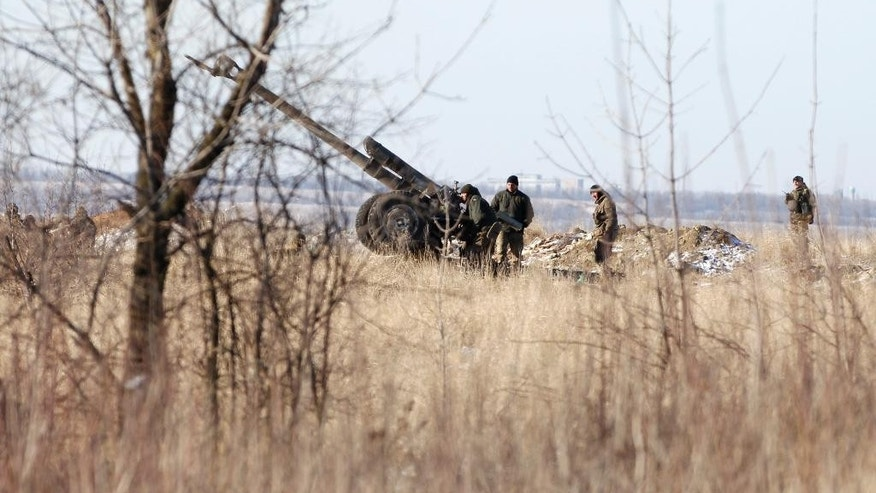 Ukrainian artillery is at a position outside of the village of Luhanske, some 20 kilometers (14 miles) north of Debaltseve, Ukraine, Tuesday, Feb. 17, 2015. Ukrainian government troops and Russia-backed rebels failed Tuesday to start pulling back heavy weaponry from the front line in eastern Ukraine as a deadline passed to do so. Under a cease-fire agreement negotiated by the leaders of Ukraine, Russia, Germany and France last week, the warring sides were to begin withdrawing heavy weapons from the front line on Tuesday. (AP Photo/Petr David Josek)