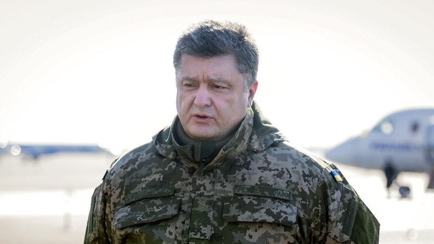 Ukrainian President Petro Poroshenko speaks to press at Borispol airport outside Kiev, Ukraine on Wednesday, Feb. 18, 2015. The army has withdrawn 80 percent of its troops from the town  Debaltseve and two more columns have yet to leave, Ukrainian President Petro Poroshenko said Wednesday. He denied claims by the rebels that the Ukrainians were surrounded and said the troops were leaving Debaltseve with their weapons and ammunition. (AP Photo/Mikhail Palinchak, Presidential Press Service)