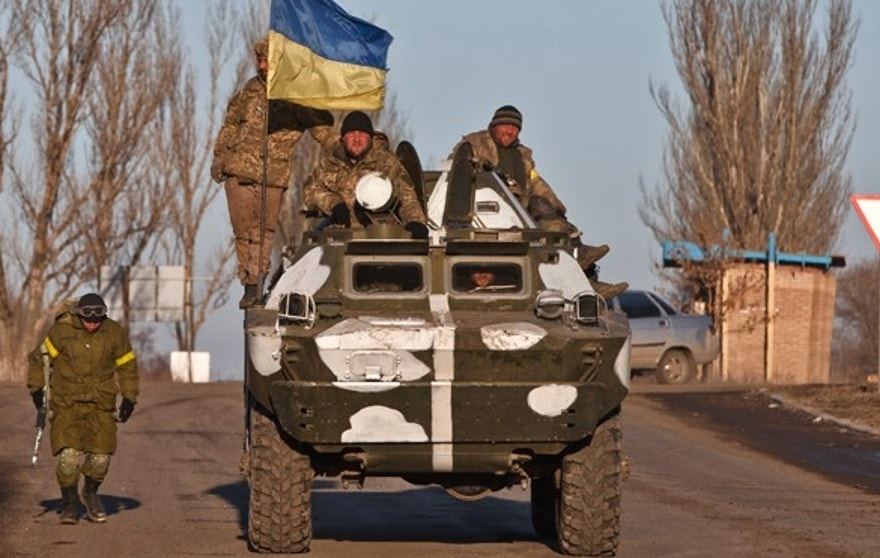 Ukrainian troops ride on an armored vehicle outside Artemivsk, Ukraine, while pulling out of Debaltseve, Wednesday, Feb. 18, 2015. After weeks of relentless fighting, the embattled Ukrainian rail hub of Debaltseve fell Wednesday to Russia-backed separatists, who hoisted a flag in triumph over the town. The Ukrainian president confirmed that he had ordered troops to pull out and the rebels reported taking hundreds of soldiers captive.(AP Photo/Vadim Ghirda)