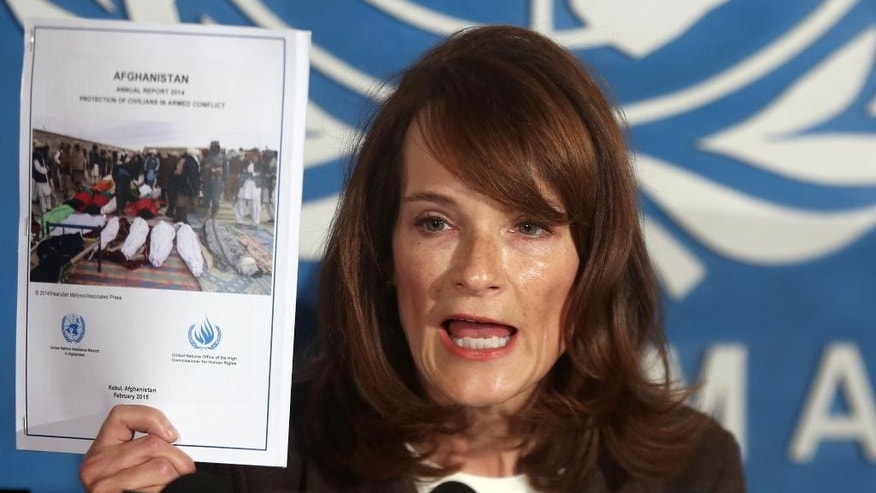 UN Human Rights Director Georgette Gagnon shows a copy of the UN report detailing civilian casualties in 2014 while speaking during a press conference in Kabul, Afghanistan, Wednesday, Feb. 18, 2015. The U.N. mission in Afghanistan says the number of civilians killed or wounded in the country's conflict climbed by 22 percent last year. In its annual report, the U.N. documents 10,548 civilian casualties in 2014, the highest total recorded in a single year since 2009. (AP Photo/Massoud Hossaini)