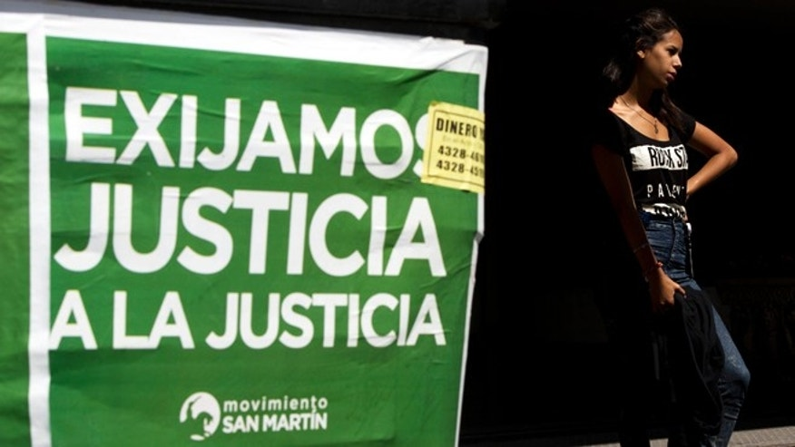 "A woman stands next to a poster that reads in Spanish ""Demand justice to justice"", in reference to march organized by federal prosecutors demanding justice after the death of special prosecutor Alberto Nisman almost a month ago, in Buenos Aires, Argentina, Friday, Feb. 13, 2015. Nisman accused President Cristina Fernandez, Foreign Minister Hector Timerman and others in her administration of brokering the cover-up in the bombing of a Jewish community center in exchange for favorable deals on oil and other goods from Iran. Fernandez and Timerman have strongly denied the accusations, and Iran has repeatedly denied involvement in the bombing, which killed 85 people. (AP Photo/Rodrigo Abd)"
