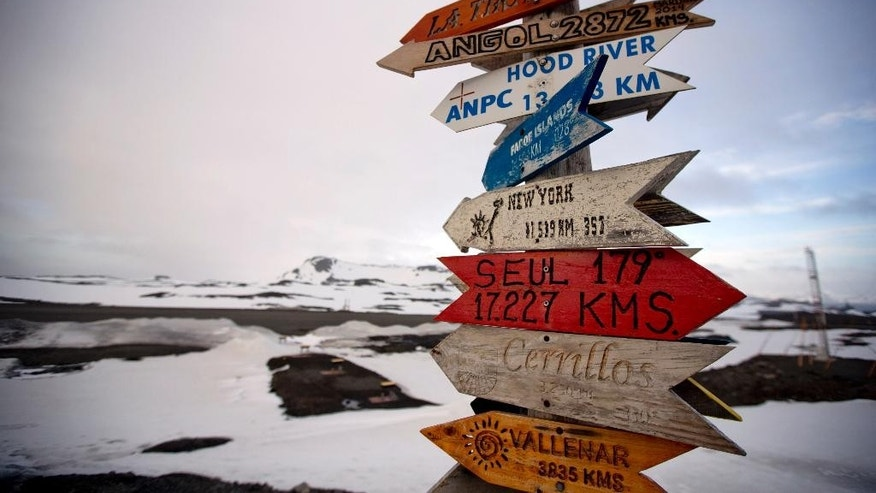 In this Jan. 20, 2015 photo, wooden arrows show the distances to various cities near Chile's Escudero station on King George Island, Antarctica. Thousands of scientists come to Antarctica for research. There are also non-scientists, chefs, divers, mechanics, janitors and the priest of the world's southernmost Eastern Orthodox Church on top of a rocky hill at the Russian Bellinghausen station. (AP Photo/Natacha Pisarenko)