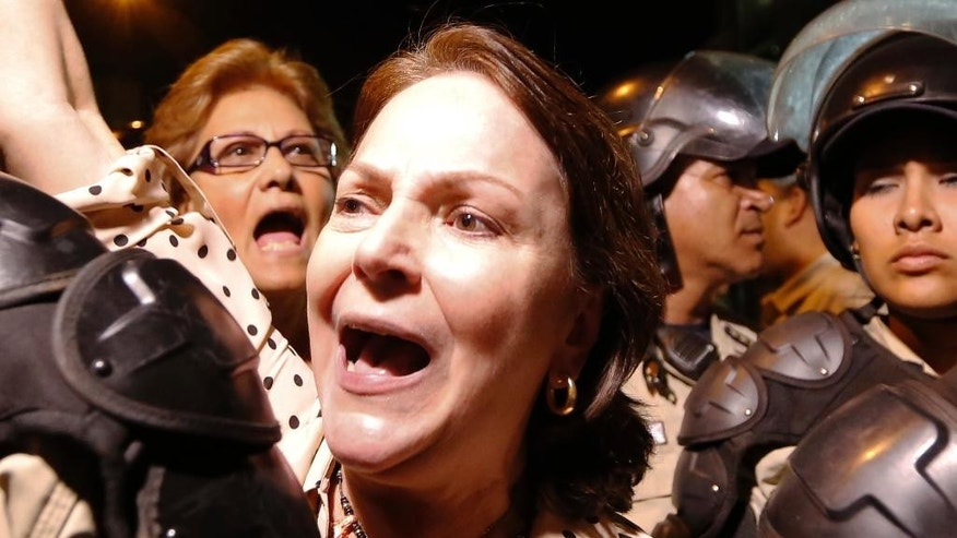 Mitzy Capriles de Ledezma, the wife of Caracas Mayor Antonio Ledezma, chants for the release of her husband outside intelligence service police headquarters, in Caracas, Venezuela, Thursday, Feb. 19, 2015. Men in camouflage uniforms smashed into Ledezma's office on Thursday and carried the opposition figure away. An aide said some of the officers wore the uniform of the national intelligence service police. (AP Photo/Ariana Cubillos)