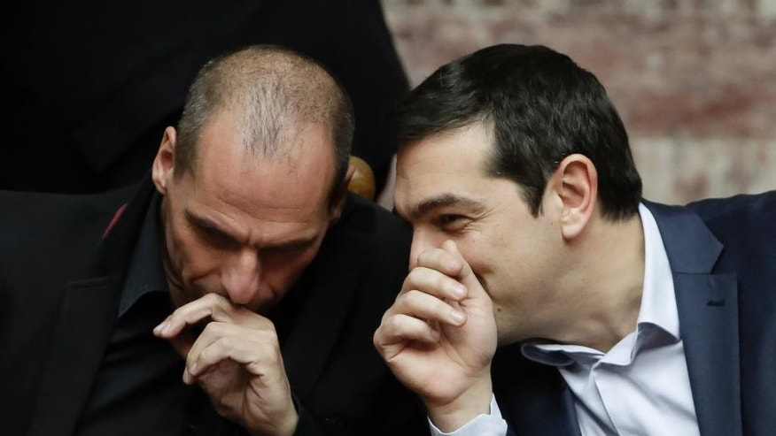 Greece's Prime Minister Alexis Tsipras chats with Greece's Finance Minister Yanis Varoufakis during a Presidential vote in Athens, on Wednesday, Feb. 18, 2015. Greece's parliament has elected conservative law professor and veteran politician Prokopis Pavlopoulos as the country's next president, after he received support from the new left-wing government and main center-right opposition party.(AP Photo/Petros Giannakouris)