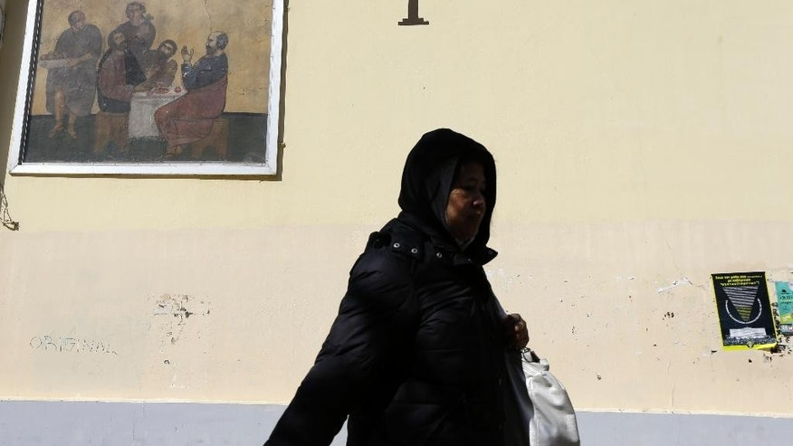 A pedestrian passes outside a small Greek Orthodox church in Athens on Thursday, Feb. 19, 2015. Greece requested Thursday a six-month extension in its rescue loan agreement — but not the associated budget measures — in a last-moment bid to break a deadlock with European creditors over its bailout program and end uncertainty over its future in the euro. (AP Photo/Thanassis Stavrakis)
