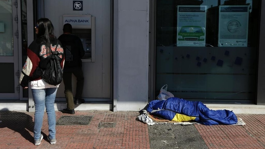 People use an ATM as a homeless man sleeps outside a bank in Athens on Thursday, Feb. 19, 2015. Greece requested Thursday a six-month extension in its rescue loan agreement — but not the associated budget measures — in a last-moment bid to break a deadlock with European creditors over its bailout program and end uncertainty over its future in the euro. (AP Photo/Thanassis Stavrakis)