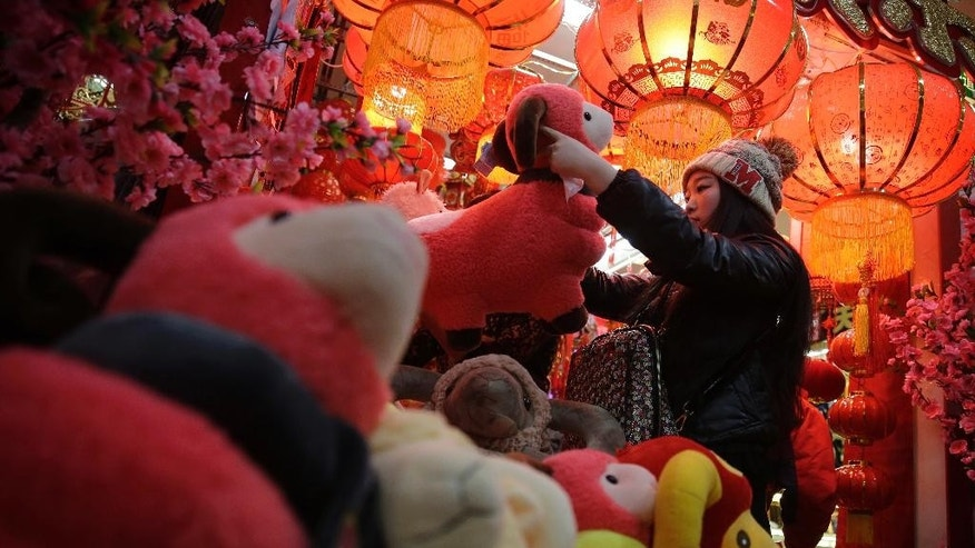 In this Feb. 12, 2015 photo, a woman shops toy sheep for Lunar New Year decorations in Beijing, China. Chinese were seeing in the Year of the Sheep on Thursday, Feb. 19 but with fortune-tellers predicting accidents and an unstable economy and some parents-to-be fretting over the year's reputation for docile kids, it wasn't exactly warming everyone's heart.(AP Photo/Andy Wong)
