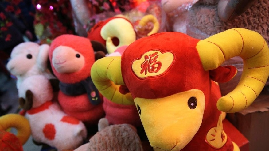 In this Feb. 12, 2015 photo, toy sheep are displayed for sale for Lunar New Year decorations in Beijing, China. Chinese were seeing in the Year of the Sheep on Thursday, Feb. 19 but with fortune-tellers predicting accidents and an unstable economy and some parents-to-be fretting over the year's reputation for docile kids, it wasn't exactly warming everyone's heart. (AP Photo/Andy Wong)