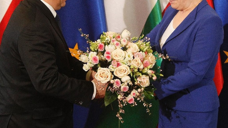 Hungary's Prime Minister Victor Orban, left, offers roses to his Polish counterpart and host Ewa Kopacz, right, before talks at Kopacz's office in Warsaw, Poland on Thursday, Feb. 19, 2015. The talks are to focus on the armed conflict in eastern Ukraine and Russia's role in it, two days after Orban's meeting with Russian President Vladimir Putin. (AP Photo/Czarek Sokolowski)