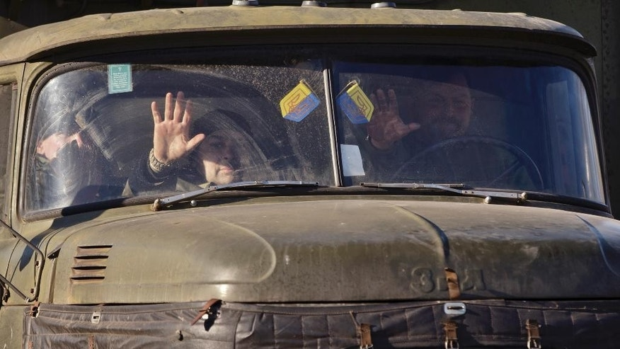 Ukrainian troops gesture from a truck outside Artemivsk, Ukraine, while pulling out of Debaltseve, Wednesday, Feb. 18, 2015. After weeks of relentless fighting, the embattled Ukrainian rail hub of Debaltseve fell Wednesday to Russia-backed separatists, who hoisted a flag in triumph over the town. The Ukrainian president confirmed that he had ordered troops to pull out and the rebels reported taking hundreds of soldiers captive. (AP Photo/Vadim Ghirda)