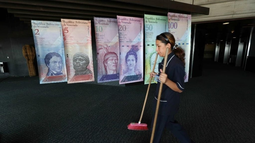FILE - In this Feb. 10, 2015 file photo, a cleaning woman walks by replicas of Venezuela's currency bills, hung in a hallway at the Central bank office building in Caracas, Venezuela. The South American country debuted a new exchange system last week aimed at easing the country's economic crisis, and on Thursday, Feb. 19, 2015, Venezuelans got their first crack at trading local cash for paper dollars at banks and money exchangers. (AP Photo/Ariana Cubillos, File)