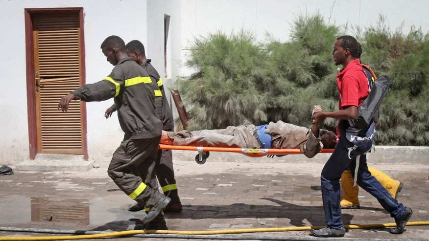 Feb. 20, 2015 - Somali rescuers carry away the dead body of a civilian from the scene of a twin bombing attack on a hotel in the capital Mogadishu, Somalia. An explosives-laden vehicle rammed into the gate of the Central Hotel in Somalia's capital, and another bomber went through the gates and blew himself up, killing at least 4.