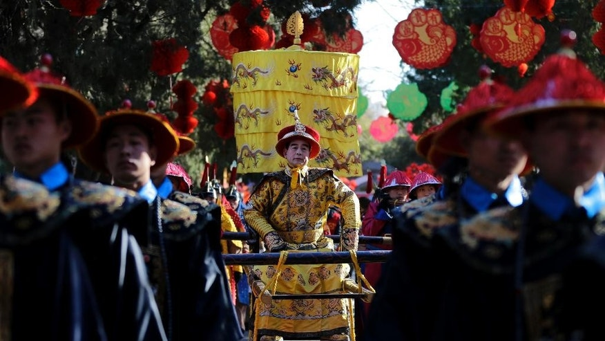 "In this photo taken Wednesday, Feb. 18, 2015, Qi Xue'en, a performer dressed as a Qing Dynasty emperor, seated at center, is carried during a re-enactment of an ancient sacrificial ceremony at Beijing's Ditan Park, the ""Altar of the Earth,"" on the eve of the Lunar New Year. Ditan Park is one of four altars dedicated to worship of the natural elements under the principles of Chinese cosmology and geomancy, popularly known as feng shui. During the seven-day Lunar New Year holiday, the parks throng with visitors shopping for festive goods, joining in carnival games and taking a break from hectic modern life. ""I have been playing the part of emperor since 1990. I have two apprentices and several pupils now,"" Qi, 58, said. ""Today and tomorrow, I will play the part of emperor, so I can send New Year's greetings to people I know. Let the pupils play on the second and third days of the Lunar New Year. I am getting old."" (AP Photo/Andy Wong)"