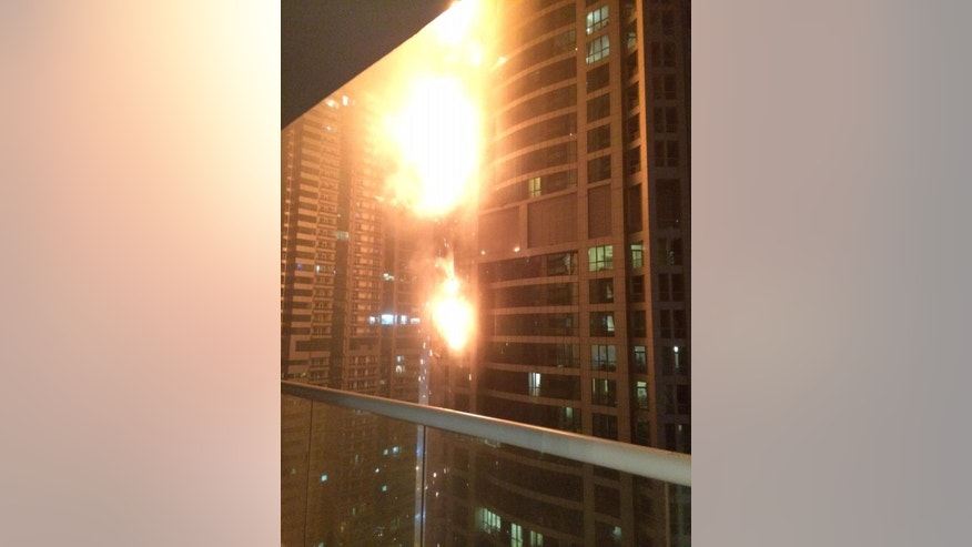This photo provided by Rhea Saran shows flames coming from a high rise tower in Dubai's marina district Saturday, Feb. 21, 2015. The fire broke out early Saturday in the Torch tower on the northeastern end of the densely populated district, which is packed with multi-story skyscrapers. Debris from the fire cluttered nearby streets after the blaze appeared to be extinguished. (AP Photo/Rhea Saran)