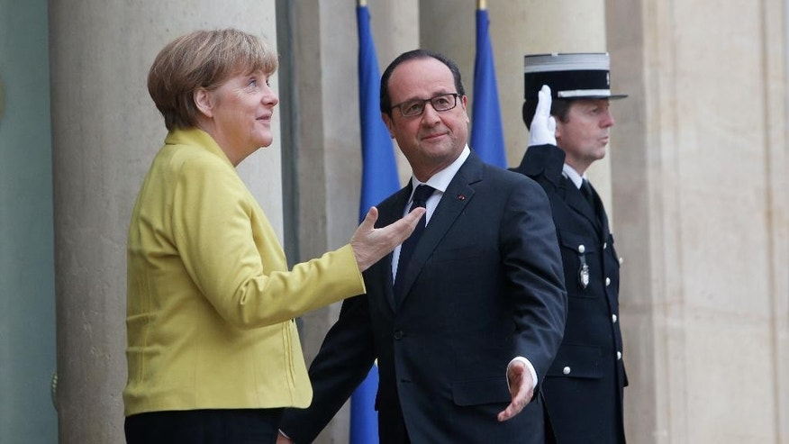 France's President Francois Hollande, right, and German Chancellor Angela Merkel, stand on the front steps of the Elysee Palace, prior to a meeting, in Paris, Friday, Feb. 20, 2015. Merkel is in Paris to discuss the crisis in eastern Ukraine and the economic stability of the eurozone. (AP Photo/Thibault Camus)