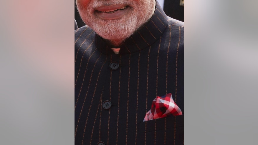 FILE - In this Jan. 25, 2015 file photo, Indian Prime Minister Narendra Modi wears a dark pinstriped suit with his name monogrammed in dull gold stripes during a reception for U.S. President Barack Obama in New Delhi, India.  Modi's suit was auctioned Friday, Feb. 20, 2015, for a whopping sum of nearly $700,000. (AP Photo/Saurabh Das, File)