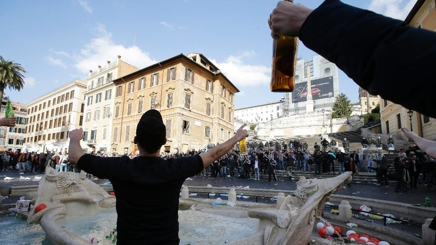 "Bottles and beer cans float in the water as Feyenoord's fans start causing troubles near the fountain called ""Barcaccia"", made by Pietro Bernini and his son Gian Lorenzo in 1627,  at the Spanish steps, in downtown Rome, prior to the Europa League soccer match between Roma and Feyenoord, Thursday, Feb. 19, 2015. The supporters rampaged through Rome's famous Piazza di Spagna on Thursday, clashing with police and injuring several officers after throwing flares and other objects. The square and the iconic Spanish Steps were left covered with beer bottles and other litter, while the recently-restored Barcaccia fountain was also damaged. (AP Photo/Gregorio Borgia)"