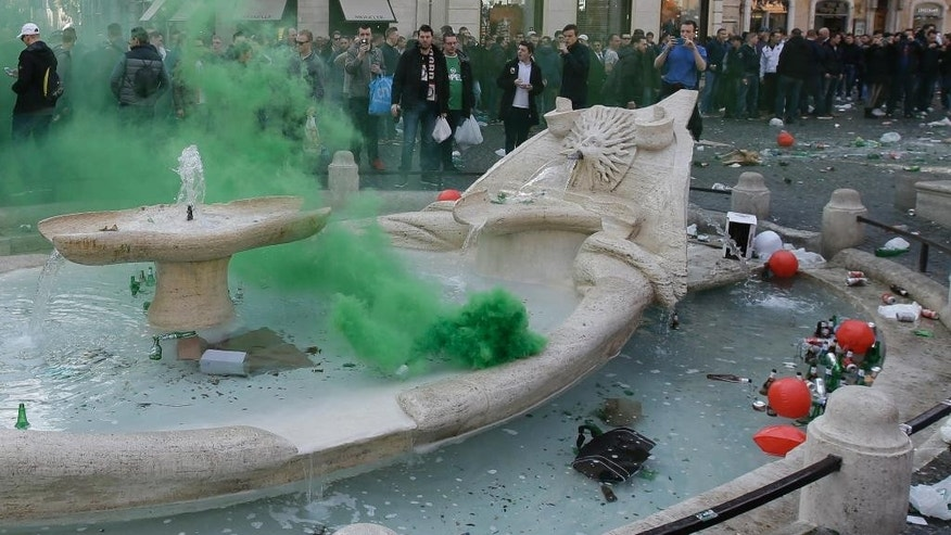 "Bottles and beer cans float in the water as a flare is thrown by Feyenoord's fans in the fountain called ""Barcaccia"", made by Pietro Bernini and his son Gian Lorenzo in 1627,  at the Spanish steps, in downtown Rome, prior to the Europa League soccer match between Roma and Feyenoord, Thursday, Feb. 19, 2015. The supporters rampaged through Rome's famous Piazza di Spagna on Thursday, clashing with police and injuring several officers after throwing flares and other objects. The square and the iconic Spanish Steps were left covered with beer bottles and other litter, while the recently-restored Barcaccia fountain was also damaged. (AP Photo/Gregorio Borgia)"