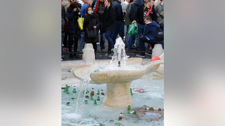 "Tourists take pictures of bottles and beer cans thrown by Feyenoord's fans in the fountain called ""Barcaccia"", made by Pietro Bernini and his son Gian Lorenzo in 1627,  at the Spanish steps, in downtown Rome, prior to the Europa League soccer match between Roma and Feyenoord, Thursday, Feb. 19, 2015. The supporters rampaged through Rome's famous Piazza di Spagna on Thursday, clashing with police and injuring several officers after throwing flares and other objects. The square and the iconic Spanish Steps were left covered with beer bottles and other litter, while the recently-restored Barcaccia fountain was also damaged. (AP Photo/Gregorio Borgia)"