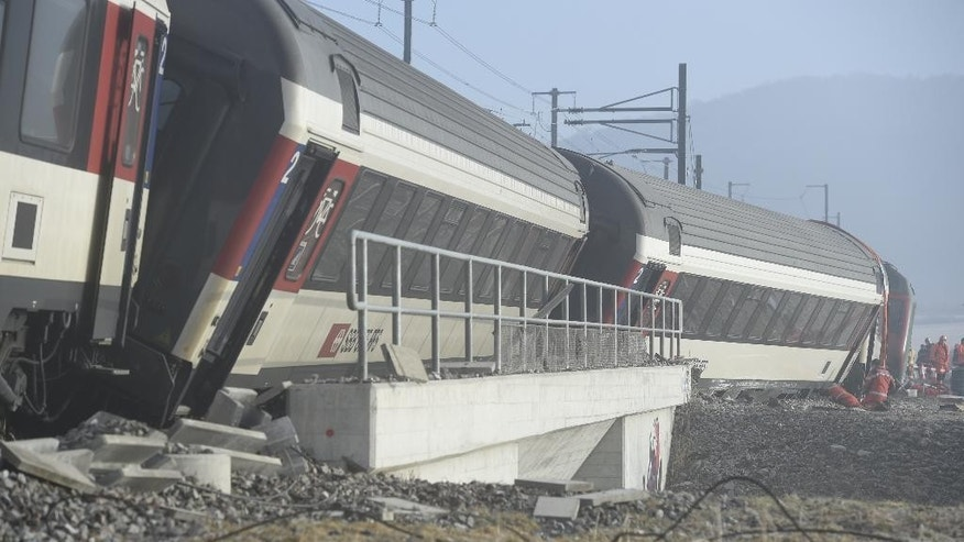 Rescue service men and firemen work at a derailed train a the accident site in Rafz, canton Zurich, Switzerland, on Friday, Feb. 20, 2015. The collision of two passenger trains in the early morning caused five injured, one of them severe, police said. (AP Photo/Keystone, Ennio Leanza)