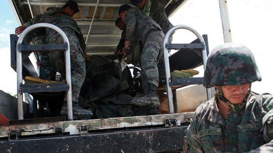 MAGUINDANAO PROVINCE, PHILIPPINES - JANUARY 26:  Policemen load into a truck the body of their comrade during a retrieval operation on January 26, 2015 in Mamasapano, Maguindanao Province, Philippines.  Dozens of elite policemen were killed after a clash with a Muslim rebel group. Lawmen would suppose serve the arrest warrants on January 25, 2015 for criminals led by Malaysian bomb maker Zulkifli bin Hir, known in military and police officials as Marwan, when the group clashed with the guerillas under Commander Guiawan of Bangsamoro Islamic Freedom Fighters, a breakaway group of the Moro Islamic Liberation, the countrys largest rebel group engaged in peace talks with Manila. The death toll of government fatalities in the fierce firefight reached fifty.  (Photo by Jeoffrey Maitem/Getty Images)