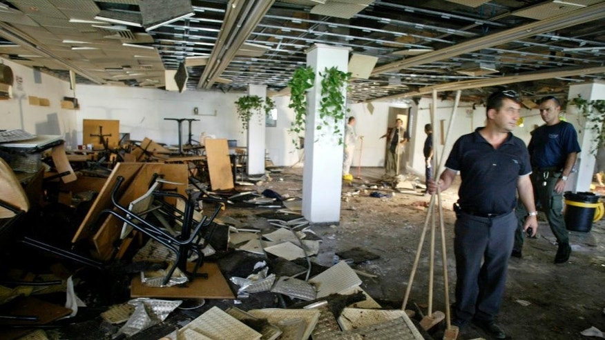 FILE - In this July 31, 2002, file photo, workers clean the inside of a cafeteria hours after a bomb exploded at Hebrew University in Jerusalem, killing nine, four of them Americans, and wounding more than 70. Palestinian officials are nervously watching a landmark terrorism trial in the U.S brought by victims of Palestinian suicide bombings and shootings aimed at civilians, fearing a negative verdict could hurt their international image at a time when they are preparing to press war crimes charges against Israel. (AP Photo/David Guttenfelder, File)