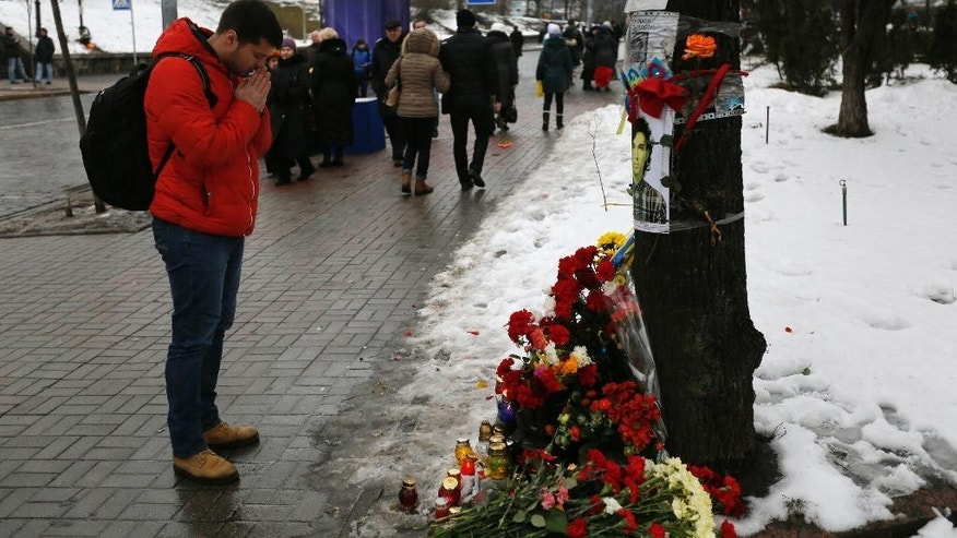"A man pay their respects in honor of the ""Heavenly Hundred"" on Independence Square in Kiev, Ukraine, Friday, Feb. 20, 2015. The ""Heavenly Hundred"" is what Ukrainians in Kiev call those who died during months of anti-government protests in 2013-14. The grisliest day was a year ago Friday _ Feb. 20, 2014 _ when sniper fire tore through crowds on the capital's main square, killing more than 50 people. A year later, so much has changed. Russia has annexed Ukraine's Crimean Peninsula, Ukraine has a new president and government, and the country is embroiled in a war in the east with Russia-backed separatists that has killed over 5,600 people and forced a million to flee. (AP Photo/Sergei Chuzavkov)"