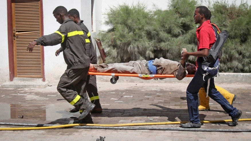 Feb. 20, 2015:  Somali rescuers carry away a severely injured civilian from the scene of a twin bombing attack on a hotel in the capital Mogadishu, Somalia.