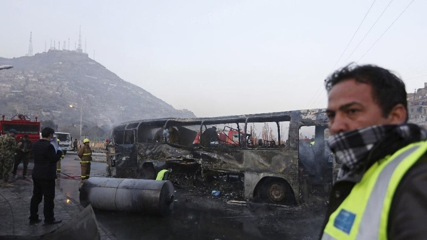 FILE - In this Dec. 13, 2014 file photo, Afghan security guards inspect a damaged bus at the site of a suicide attack by the Taliban in Kabul, Afghanistan. The Afghan government is set to open a dialogue with Taliban insurgents it has been fighting for more than a decade, officials, diplomats and experts said. Speaking at a joint press conference with visiting U.S. Defense Secretary Ash Carter, President Ashraf Ghani, declared Saturday, Feb. 21, 2015, that peace is closer now than at any time since the war began following the September 11, 2001 attacks on the U.S.  (AP Photo/Rahmat Gul, File)