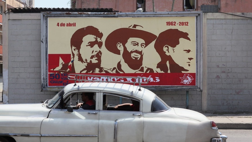 HAVANA, CUBA - MARCH 26:  A billboard celebrating some of Cuba's revolutionary heroes (L-R) Che Guevara, Camilo Cienfuegos and Julio Mella , hangs on a wall on the day that Pope Benedict XVI is scheduled to arrive in Cuba on March 26, 2012 in Havana, Cuba. Pope Benedict, who will be arriving from Mexico, will conduct a mass in the city of Santiago de Cuba first followed by a mass in Havana before leaving on the March 28.Tensions are high in Cuba between some dissidents and the government as activists hope the international exposure of the Papal visit will result in renewed attention to their struggle  (Photo by Joe Raedle/Getty Images)