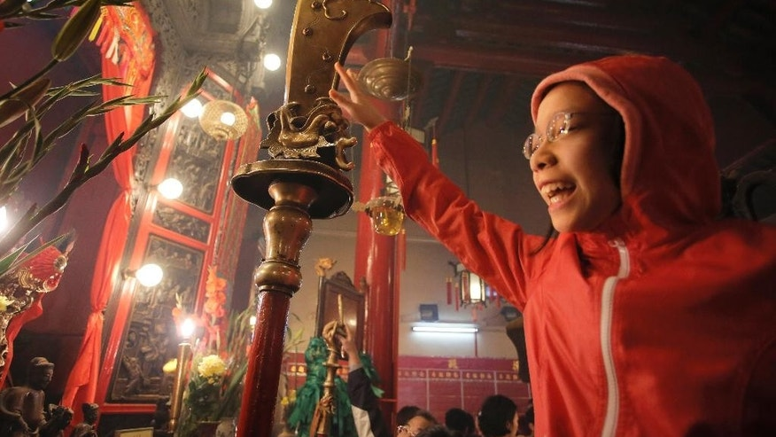 """In this photo taken on Friday, Feb. 20, 2015, Annie leung, 12, is lifted by her father to touch a guandao - a type of traditional Chinese weapon - in a gesture that is supposed to bring good fortune in the coming year, at Man Mo Temple in central Hong Kong. The temple pays tribute to the God of Literature (""""Man"""" in Chinese) and God of War (""""Mo"""" in Chinese) traditionally worshipped by scholars in ancient China looking to succeed and excel in civil examinations that would win them high positions in the government. Annie was spending time with her family over the Chinese New Year holiday and offered her prayers at this Hong Kong temple on the second day of the Chinese Lunar New Year.  """"My new year wish is to achieve good results in school this year,"""" she said. (AP Photo/Vincent Yu)"""