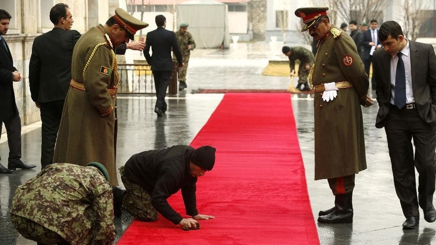 The red carpet gets a final cleaning before an Afghan military honor welcomes U.S. Defense Secretary Ash Carter at the Presidential Palace in Kabul, Afghanistan Saturday, Feb. 21, 2015. (AP Photo/Jonathan Ernst, Pool)