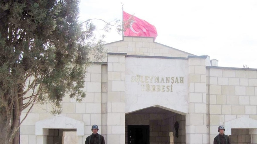 FILE - In this April 7, 2011 file photo, Turkish soldiers stand guard at the entrance of the memorial site of Suleyman Shah, grandfather of Osman I, founder of the Ottoman Empire, in Karakozak village, northeast of Aleppo, Syria. Turkey's state-run TRT television broadcaster reported early Sunday Feb. 22, 2015 that Turkey launched the operation overnight to evacuate troops guarding an Ottoman tomb in Syria, just over the border near the town of Kobani. (AP Photo/File)