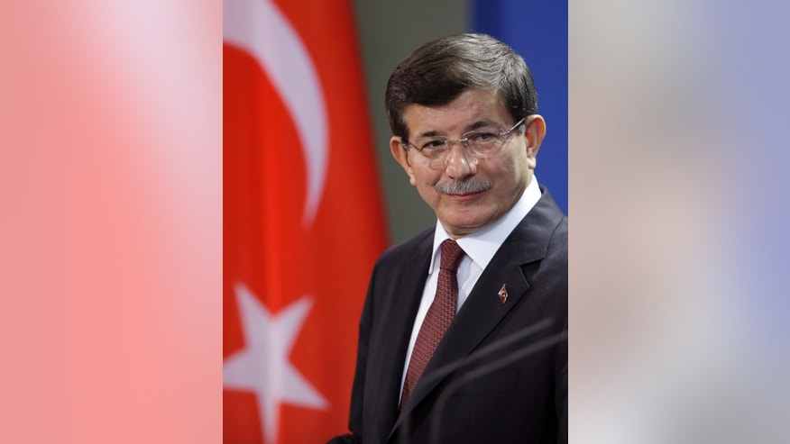 FILE - The Prime Minister of Turkey, Ahmet Davutoglu, attends a joint news conference with German Chancellor Angela Merkel after a meeting at the chancellery in Berlin, Germany, in this, Jan. 12, 2015 file photo. Turkey's prime minister said early Sunday Feb. 22, 2015 his country has evacuated troops guarding an Ottoman tomb in Syria. (AP Photo/Michael Sohn, File)