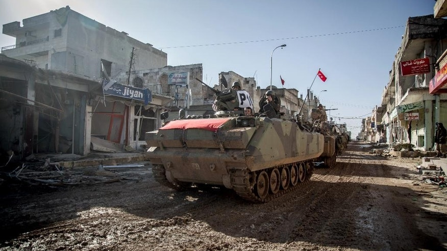 Turkish army's armored vehicles and tanks drive in Syrian town of Ayn al-Arab, also known as Kobani, as they return from the Ottoman tomb in Syria, Sunday, Feb. 22, 2015. Turkey launched an overnight military operation into neighboring Syria to evacuate troops guarding an Ottoman tomb and to move the crypt to a new location, Turkish Prime Minister Ahmet Davutoglu said Sunday. Davutoglu said nearly 600 troops and 100 tanks and armored personnel carriers were involved in the operation. One group crossed into Syrian territory to reach the tomb, just over the border near the town of Kobani, while a second group took control of an area near the Turkish border where authorities plan to move the tomb.(AP Photo/Mursel Coban, Depo Photos)