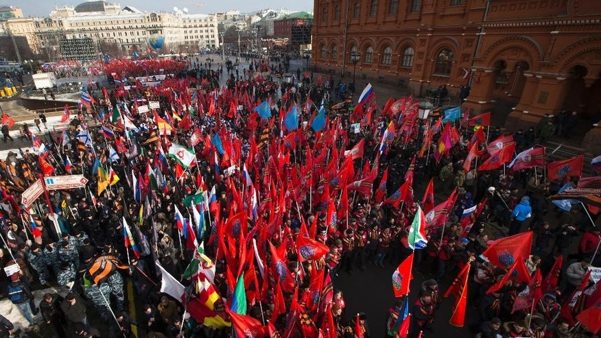 Activists from Russia's Anti-Maidan movement gather together waving various patriotic flags in central Moscow, Russia, Saturday, Feb. 21, 2015, to mark an anniversary of Ukraine's pro-EU protests that started on Kiev's central Independence Square, widely known as the Maidan. (AP Photo/Ivan Sekretarev)