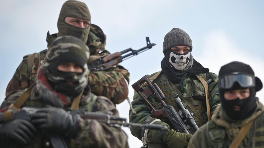A Russia-backed rebel fighter holds a sniper rifle while wearing a mask in Debaltseve, Ukraine, Friday, Feb. 20, 2015. After weeks of relentless fighting, the embattled Ukrainian rail hub of Debaltseve fell Wednesday to Russia-backed separatists, who hoisted a flag in triumph over the town. The Ukrainian president confirmed that he had ordered troops to pull out and the rebels reported taking hundreds of soldiers captive.(AP Photo/Vadim Ghirda)